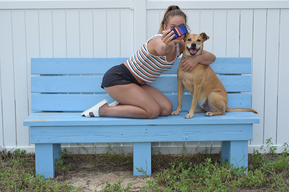 Photo of girl taking a selfie on a bench next to dog